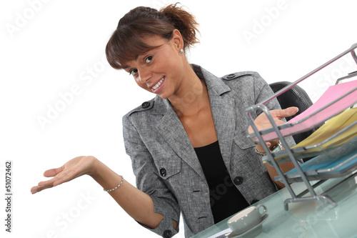 Happy receptionist presenting her work area