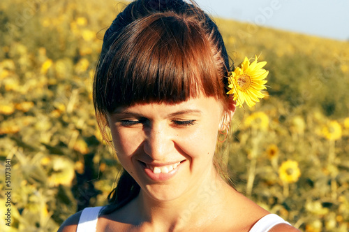 Young happy woman on the sun and sunflowers