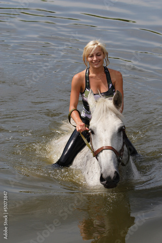 Girl swiming with her horse
