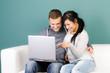 junges paar schaut glücklich auf einen laptop