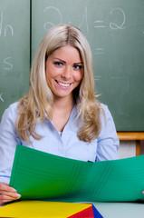 freundliche grundschullehrerin korrigiert hausaufgaben