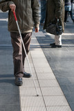 Blind person with white cane in public space