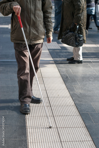 Poster Blind person with white cane in public space