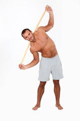 Man exercising with a wooden stick