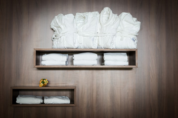 bathrobes and towels stapled on brown wooden shelf with flowers