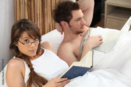 Young woman reading book and man using laptop in bed