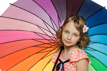 Closeup of little girl standing under colorful umbrella