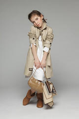 Little girl wearing trench coat holding handbag