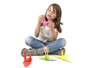 Cute girl makes origami birds
