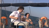 Young couple for yacht steering wheel