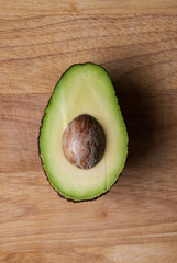 Half and avocado on wooden chopping board