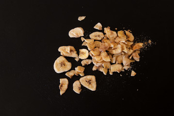 Dried banana scattered on a black background