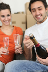 couple opening bottle of champagne