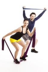 Zwei lachende Sportler trainieren begeistert mit Theraband