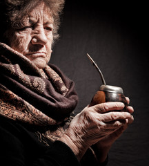 portrait of an old woman with Argentinean calabash in hands
