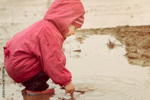 little girl playing in the puddle