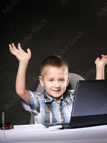 Triumphing child with a laptop computer