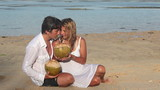 couple with coconuts have dating at tropical beach