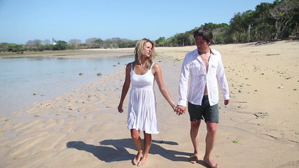 Happy couple holding by hands and walking together at beach