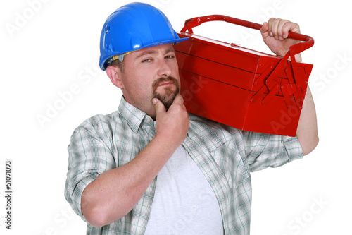 craftsman holding a tool box and touching his chin