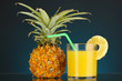 Ripe pineapple and juice glass on dark blue background