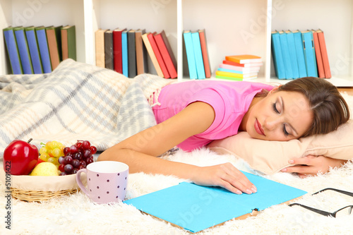 Young female asleep while reading book on floor