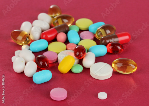 Assortment of pills, tablets and capsules on red background