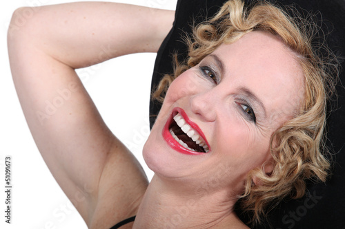 Close up of laughing woman in red lipstick and a black hat