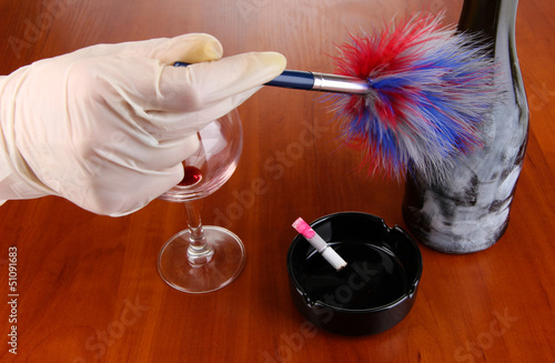 Taking fingerprints with bottle of wine on wooden table