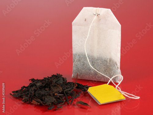 Tea bag on red background