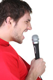 Profile of a man singing into a microphone