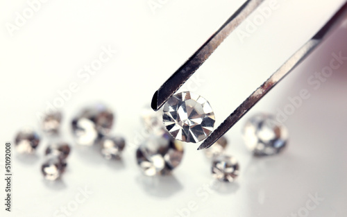Beautiful shining crystal (diamond) in the tweezers, isolated