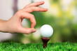 Hand pushing golf ball on green grass outdoor close up