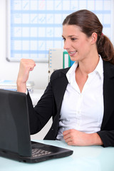 businesswoman delighted with what she can see on her computer