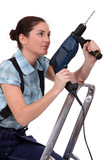 Woman holding drill whilst climbing ladder