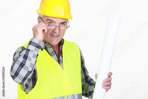A mature foreman holding plans.