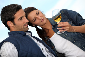 Couple looking at a glass of alcohol