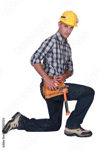 Builder kneeling