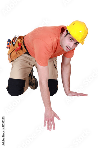 Kneeling tradesman reaching down
