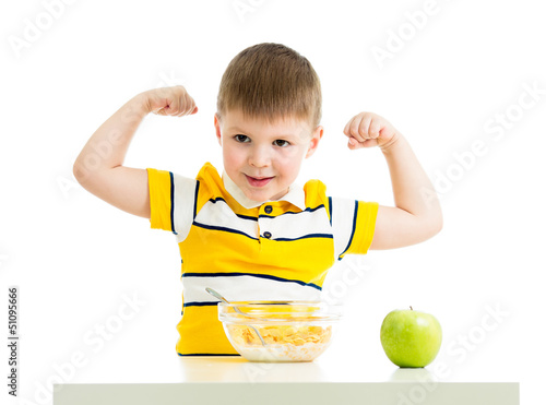 kid boy eating healthy food and showing strength