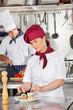 Female Chef Garnishing Dish In Kitchen