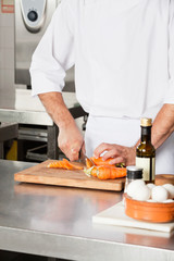 Chef Cutting Carrots At Kitchen Counter