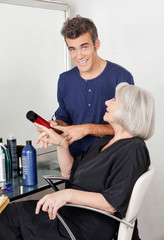 Hairdresser Showing Hair Product To Client