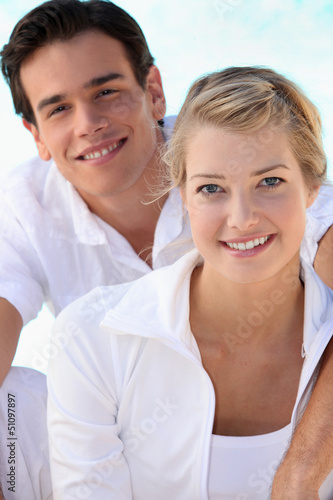 Smiling young couple dressed in white on a summer's day