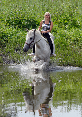 Pretty girl bathe horse in a river