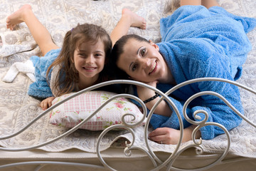 Mom and daughter lay down on the bed