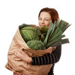 Woman holding a paper shopping bag with green vegetables