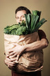 Man holding bag full of green vegetables