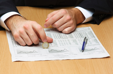 Businessman putting the coins on a diagram