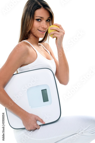 young and thin woman with an apple and a bathroom scale